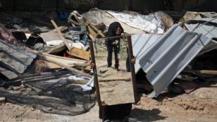 امرأة من البدو تحمل مرآة بعد هدم منزلها في قرية خان الأحمر في الضفة الغربية في 7 نيسان/أبريل 2016.