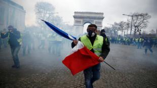 Un manifestant brandit un drapeau français alors que l'avenue des Champs-Élysées se remplit de gaz lacrymogènes.