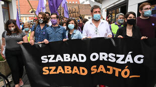 """Protesters hold a banner with the slogan """"Free country, free press"""" after the editor of an independent news site was sacked prompting a mass staff walk out"""