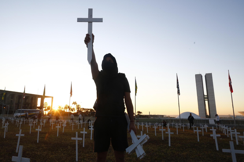 """En Brasilia, unos manifestantes colocaron 1.000 cruces en el césped frente al Congreso para rendir homenaje a las víctimas del coronavirus, con una pancarta que rezaba: """"Bolsonaro, ¡deja de negar!"""""""