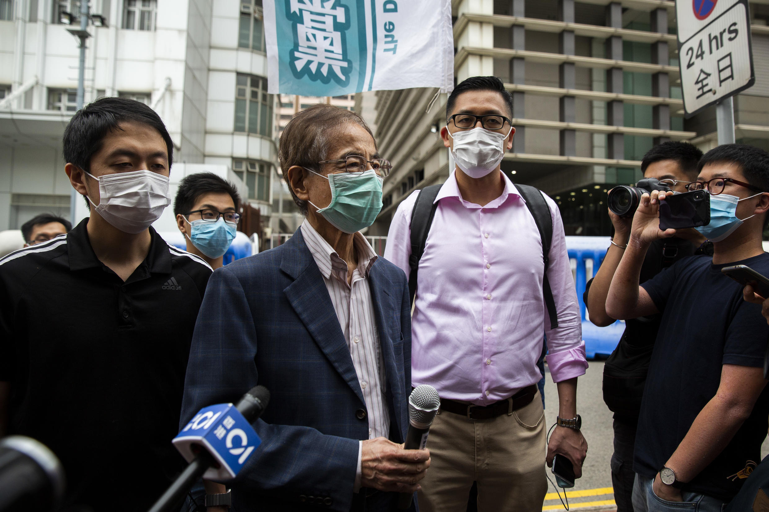 Former lawmaker and pro-democracy activist Martin Lee (centre L) talks to the media as he leaves the Central District police station in Hong Kong on April 18, 2020.