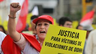 """Un manifestante sostiene un letrero que dice: """"justicia para las víctimas de violaciones de derechos humanos"""" durante una marcha contra el perdón del ex presidente Alberto Fujimori en Lima, Perú, el 11 de enero de 2018."""
