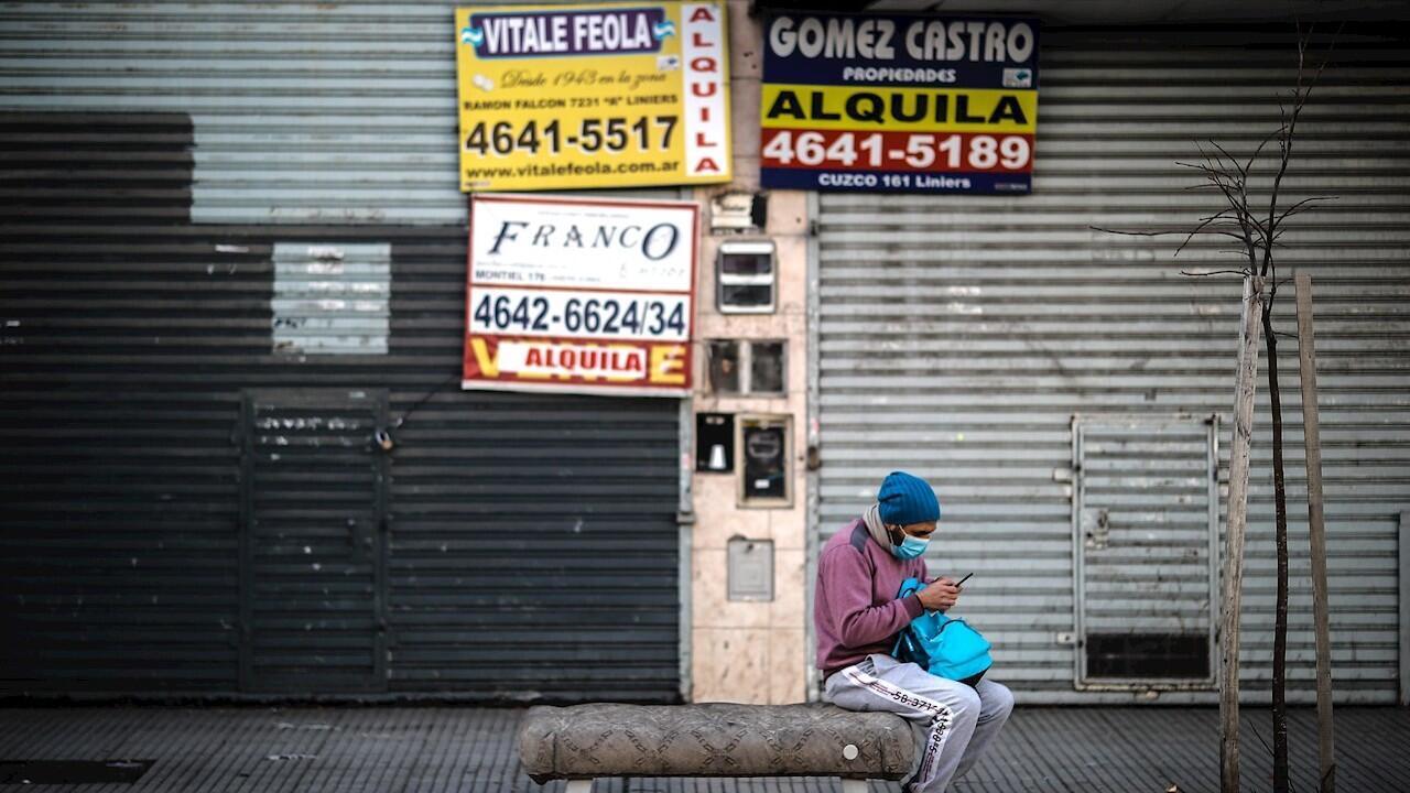 Un hombre revisa su celular frente a locales comerciales cerrados este miércoles, en Buenos Aires (Argentina). Tras registrarse un aumento en el número de contagios de coronavirus, Buenos Aires y su populoso cinturón urbano dan marcha atrás y entran en nueva fase de la cuarentena, más estricta y hasta el 17 de julio.