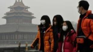 سياح صينيون يرتدون أقنعة واقية خلال تجولهم في بكين في 26 شباط/فبراير 2014