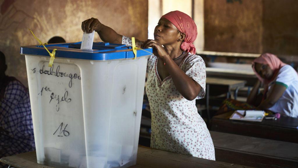 Une femme glisse son bulletin dans l'urne dans un bureau de vote à Bamako, le 12 août 2018.