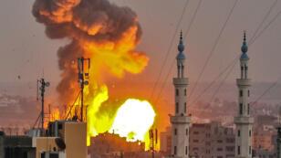 Una foto tomada el 20 de julio de 2018 muestra una bola de fuego explotar en la ciudad de Gaza durante el bombardeo israelí. Aviones y tanques israelíes atacaron objetivos en la Franja de Gaza el 20 de julio luego de disparar contra las tropas en la frontera, dijo el ejército.