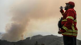 Un bombero se hidrata mientras observa una colina donde el fuego se ha reactivado en Monchique, Algarve, sur de Portugal, hoy, 6 de agosto de 2018. Unos 800 bomberos, 220 vehículos y diez aeronaves participan en las labores de extinción