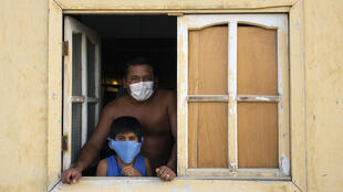 Residentes de la comunidad de El Diablo, cerca de la norteña ciudad de Piura, en Perú, miran por la ventana mientras las autoridades realizan un registro de familias que reciben donaciones de alimentos en sus casas el 27 de abril de 2020