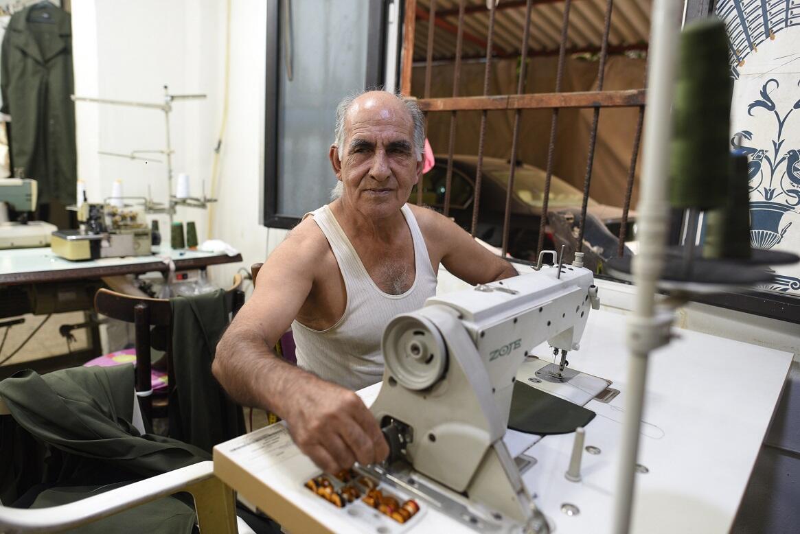 عامل أرميني في مجال الخياطة أمام آلته