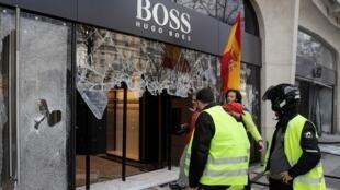 La vitrine d'un magasin Hugo Boss brisée par des Gilets jaunes, samedi 16 mars, sur les Champs-Élysées, à Paris.