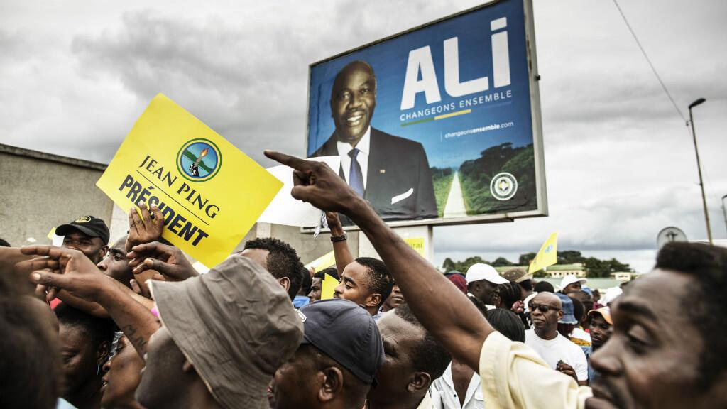 Des militants pro-Jean Ping manifestent dans les rues de Libreville, vendredi 26 août 2016, sous une affiche de campagne du président sortant Ali Bongo.