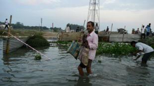 Un habitant essayant de sauver ses biens des inondations à Malda, au Bengale, le 21 août.