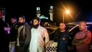 سكان ينتظرون طلب الشرطة منهم إخلاء المنطقة قرب مسجد الإمام الحسين ببلدة فيرولام خارج مدينة دوربان 13 أيار/مايو 2018