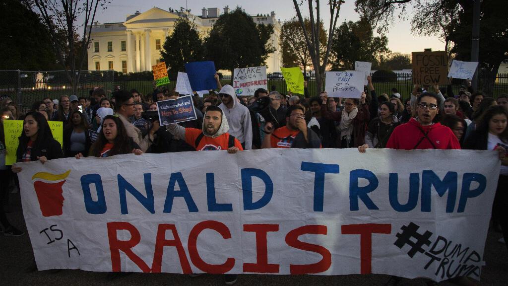 """متظاهرون يرفعون لافتة كتب عليها """"دونالد ترامب عنصري"""""""