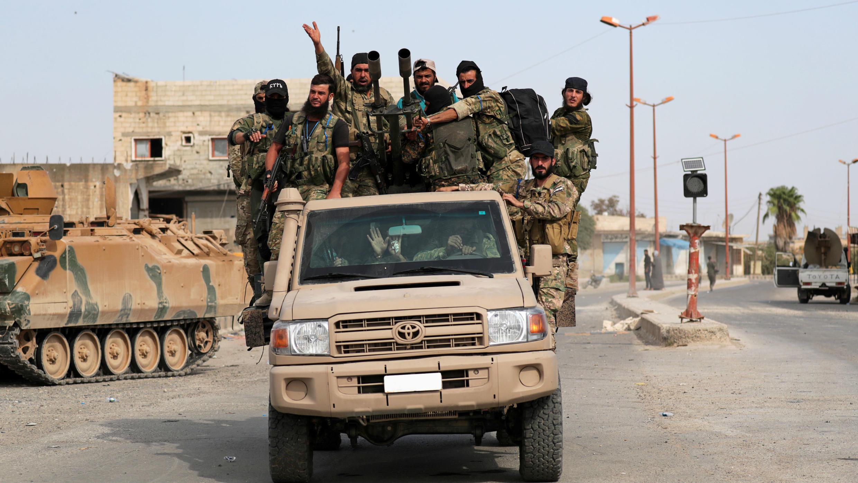 Los combatientes rebeldes sirios respaldados por Turquía viajan en un vehículo en la ciudad fronteriza de Tel Abyad, Siria, el 14 de octubre de 2019.