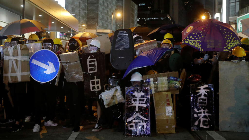 Manifestantes se enfrentan con la policía con paraguas y cascos.