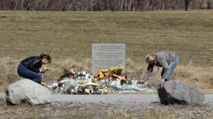 Au Vernet (Alpes-de-Haute-Provence), des femmes déposent des fleurs au pied du mémorial pour les victimes du crash.