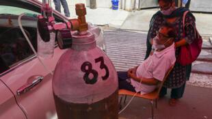 أحد المصابين بكوفيد-19 موصول بقارورة أكسجين في غازي ىباد بولاية اوتار براديش الهندية، في 28 نيسان/أبريل 2021
