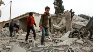 Des enfants syriens errent parmi des débris à la suite d'un raid aérien sur la Ghouta, le 15 février 2018.