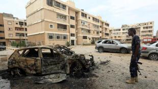 مقاتل موالي لحكومة الوفاق الوطني في ليبيا، يقف أمام هيكل سيارة مدمرة نتيجة قصف يوم 9 أيار/مايو 2020 غي حي بن غشير في طرابلس
