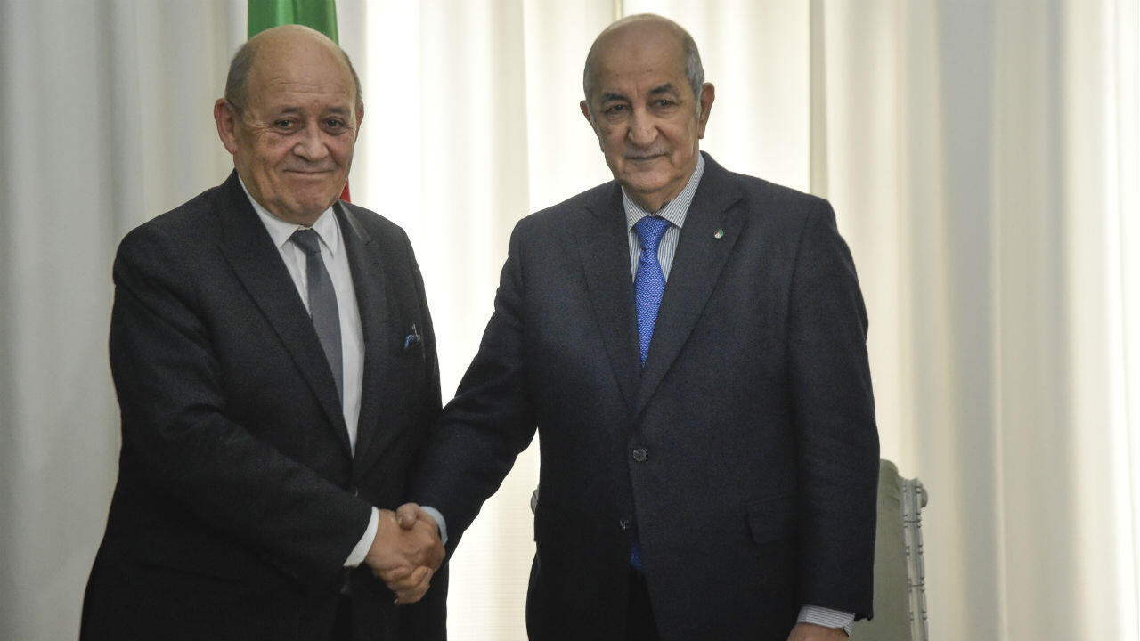 Le président algérien Abdelmadjid Tebboune serre la main au ministre français des Affaires étrangères Jean-Yves Le Drian en visite à Alger, la capitale, le 21 janvier 2020.