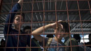 De jeunes garçons gettent l'arrivée d'un train dans un camp pour réfugiés en Macédoine, le 17 septembre 2015.