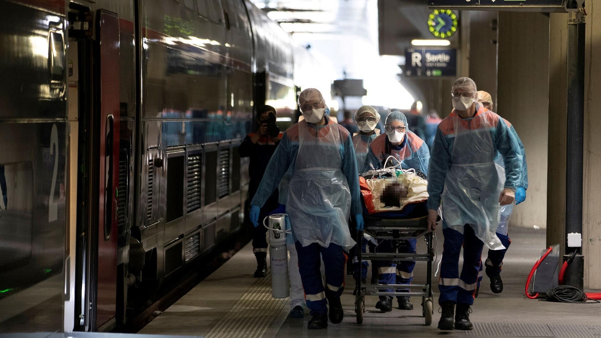 فريق طبي يرافق مصابا بفيروس كورونا إلى قطار بمحطة أوسترليتز بباريس لنقله إلى مستشفى بمقاطعة بروتاني، 1 أبريل/نيسان 2020.