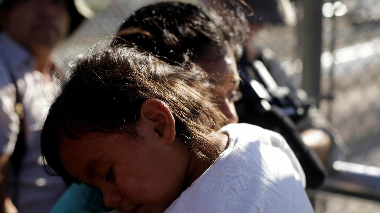 Una familia migrante de México, huyendo de la violencia, espera ingresar a Estados Unidos para reunirse con oficiales de Aduanas y Protección Fronteriza de los EE. UU. Para solicitar asilo en el puente fronterizo internacional Paso del Norte en Ciudad Juárez el 20 de junio de 2018.