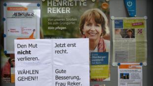 """Des affichettes aposées contre une affiche de campagne de la candidate poignardée, Henriette Reker, sur lesquelles on peut lire """"Allez voter ! Plus que jamais. Bonne convalescence Mme Reker""""."""