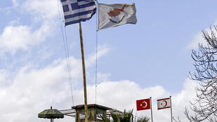 The flags of Greece, Cyprus, Turkey and the self-proclaimed Turkish Republic of Northern Cyprus (TRNC) fly above security outposts in the divided Cypriot capital Nicosia