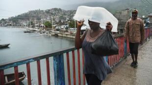 Une résidente de Cap-Haïtien, à Haïti, s'abrite de la pluie à l'approche du cyclone Irma, le 7 septembre 2017.