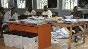 Des membres de la Ceni examinent les premiers résultats de l'élection présidentielle guinéenne, mercredi 14 octobre 2015, à Conakry.
