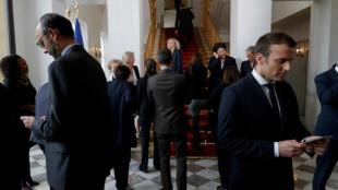 Le président Emmanuel Macron et son Premier ministre Édouard Philippe sur leurs smartphones.