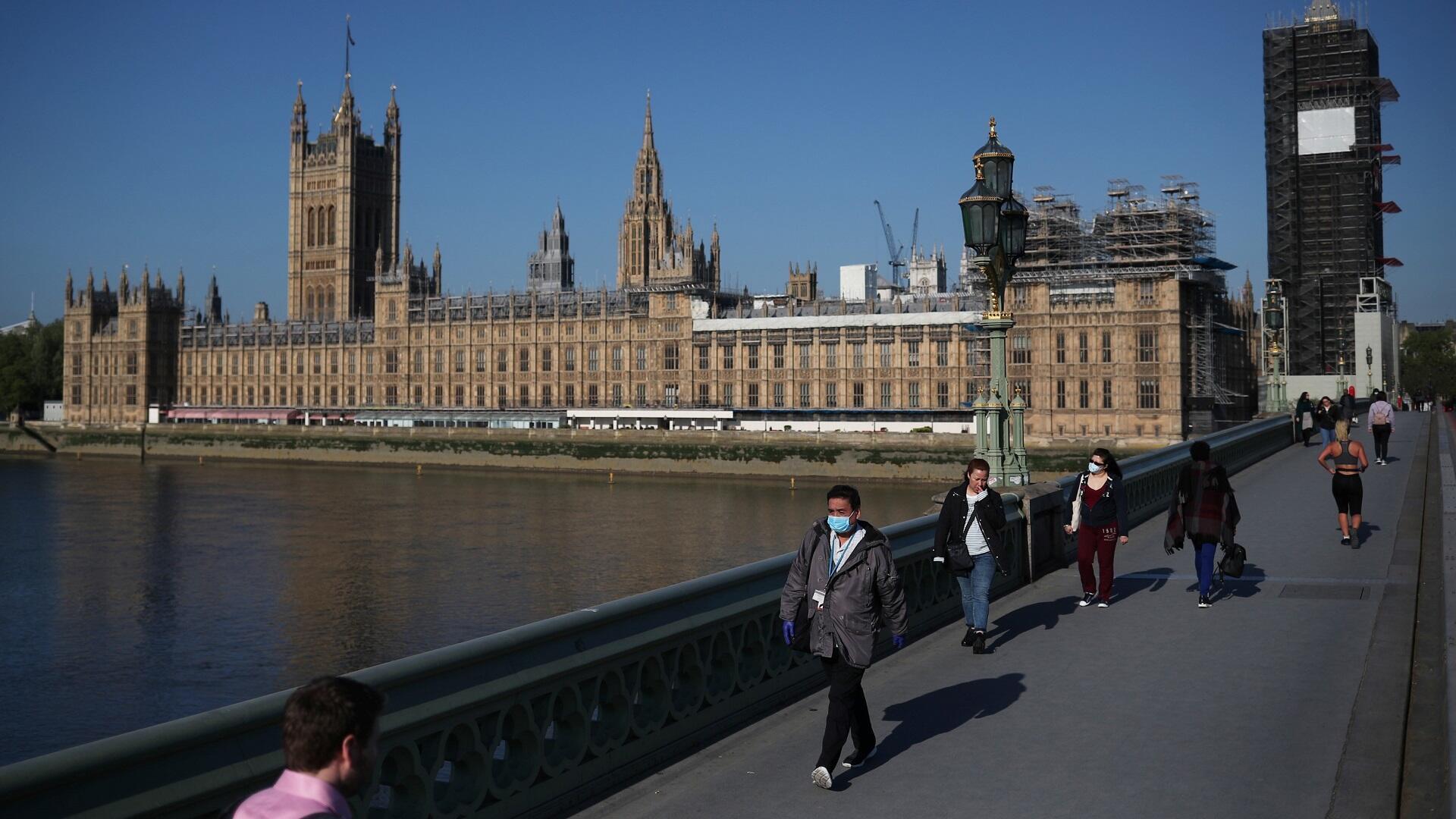 Las personas caminan por el puente de Westminster en Londres, el 6 de mayo de 2020.
