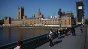 بريطانيون يسيرون على جسر ويستمنستر بلندن وبعضهم يرتدي كمامات للوقاية من فيروس كورونا، 6 مايو/أيار 2020.