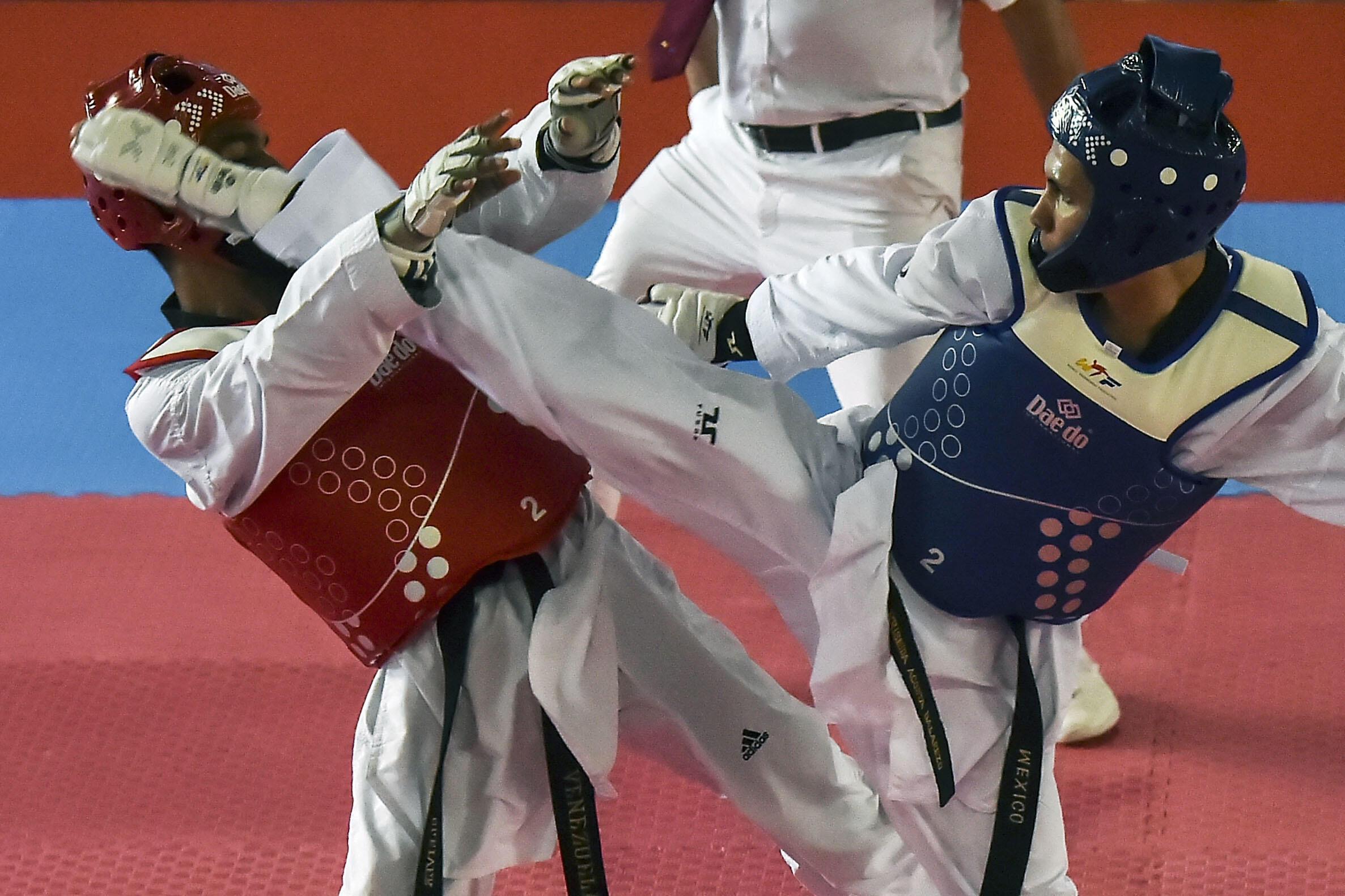 El atleta venezolano Cleiver Olaizola compite contra el mexicano César Rodríguez en taekwondo hasta los 54 kg.
