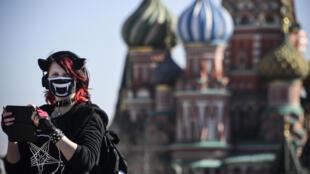 فتاة ترتدي قناعاً واقياً في الساحة الحمراء في موسكو في 25 آذار/مارس 2020
