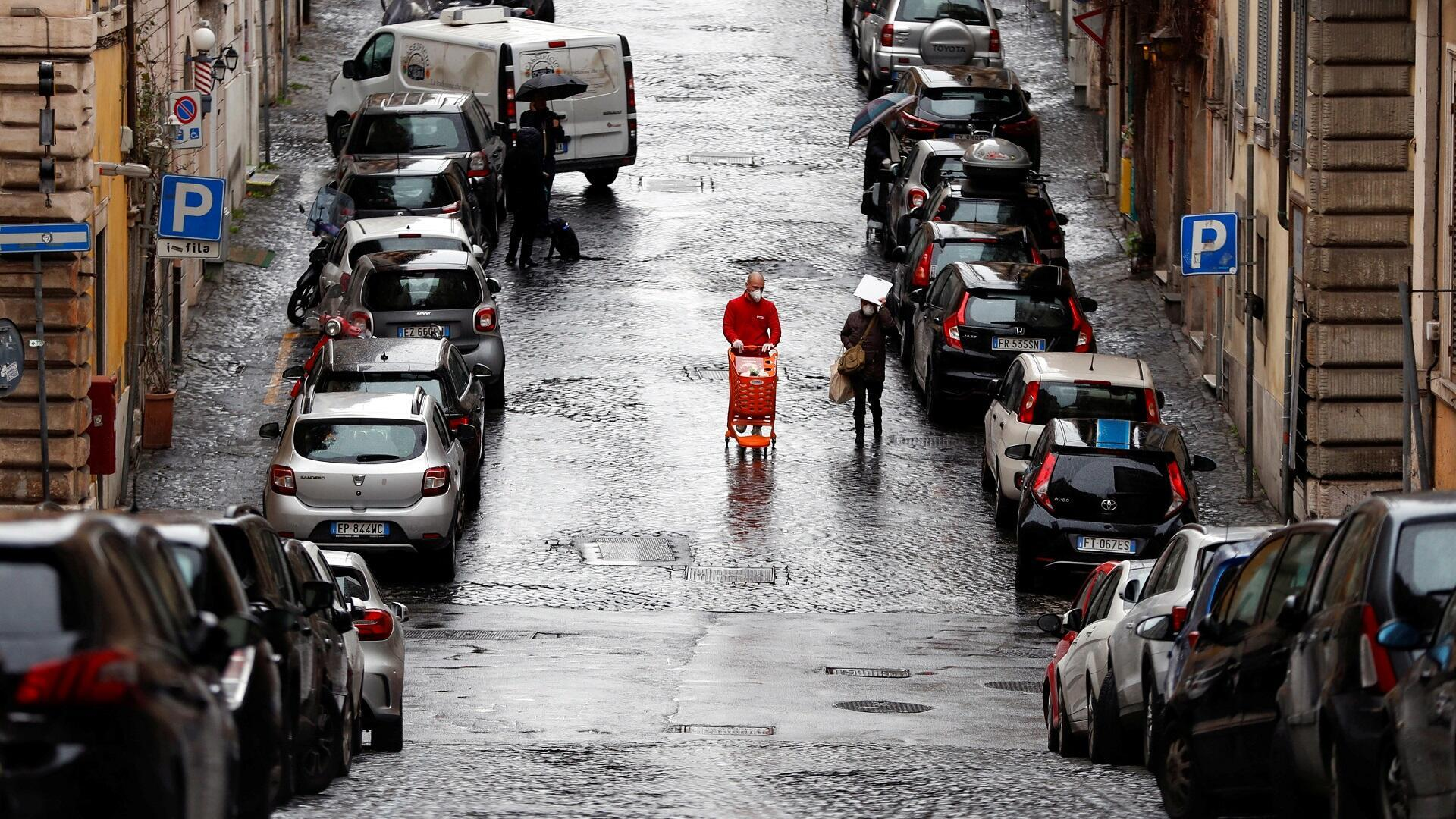 Un hombre usa un hocico y empuja un carrito de compras frente a él en una calle semivacía en la capital italiana, Roma, el 26 de marzo de 2020.
