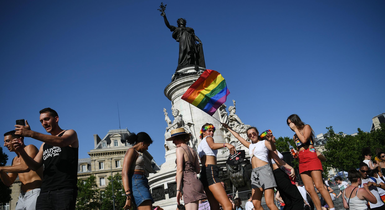 Participantes de la marcha del orgullo gay posan con una bandera del arco iris frente a la Estatua de Marianne en la plaza Place de la Republique,en París, Francia, el 29 de junio de 2019.
