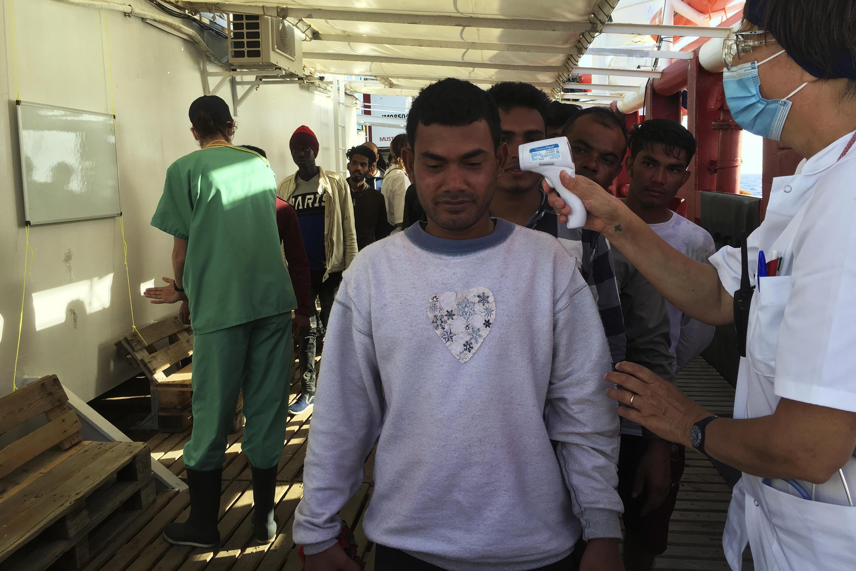 Anne, médica de la ONG francesa SOS Méditerranée, toma la temperatura de los migrantes rescatados por miembros del barco 'Ocean Viking', frente a la costa de la isla italiana de Lampedusa.
