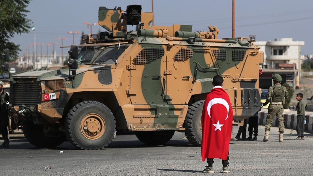 Un niño con una bandera turca se para frente a un vehículo militar turco en la ciudad de Tal Abyad, Siria, el 23 de octubre.