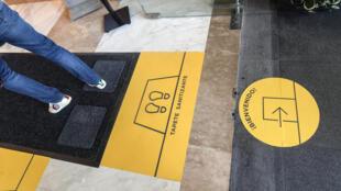 Un cliente entra en una alfombra desinfectante en un centro comercial en el barrio de Polanco, Ciudad de México el 8 de julio de 2020, durante la pandemia de covid--19