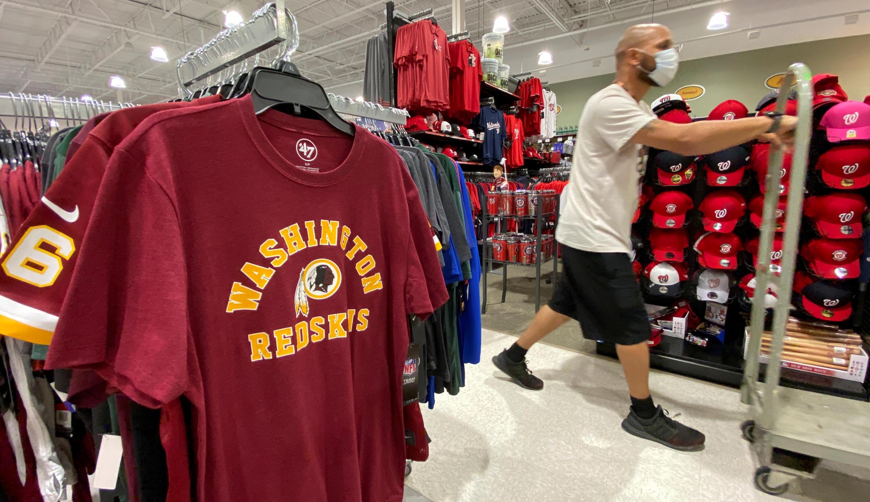 Un empleado pasa junto a camisetas de Washington Redskins a la venta en una tienda deportiva de Virginia, Estados Unidos, el 24 de junio de 2020.