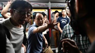 Altercation entre un passager du métro hongkongais et un manifestant qui tentait d'empêcher la fermeture des portes, à la station Fortress Hill à HongKong, le 5août2019.
