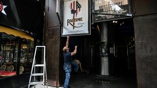Employees remove movie posters outside The Max Linder Cinema Theatre in Paris on June 18, 2020, ahead of the re-opening of cinema halls and theatres, as France eases lockdown measures taken to curb the spread of the Covid-19 pandemic (novel coronavirus).
