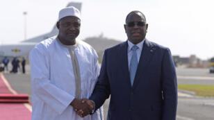 Adama Barrow (à gauche) accompagné par le président sénégalais Macky Sall (à droite) sur le tarmac de l'aéroport de Dakar d'où son avion s'est envolé pour la Gambie.