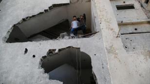 Ciudadanos palestinos se ven fuera de su casa que fue dañada tras un ataque aéreo de Israel, en la ciudad de Gaza el 13 de noviembre de 2018.