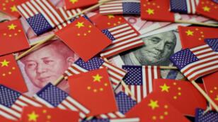 Un billete de dólar con la imagen del padre fundador americano, Benjamin Franklin, y uno chino con la imagen del expresidente Mao Zedong, entre banderas chinas y estadounidenses. 20 de mayo de 2019.