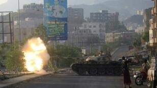 Yemeni fighters loyal to exiled President Abedrabbo Mansour Hadi fire from a tank during clashes with Shiite Huthi rebels in the country's third-city of Taez
