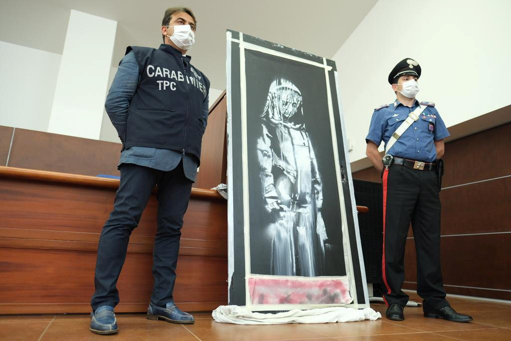 Italian Carabinieri military police stand by a mural attributed to British street artist Banksy that was stolen from the Bataclan theatre in Paris, where Islamist militants killed 90 people in 2015, after it was found in a farmhouse in central Italy, in L'Aquila, Italy, June 11, 2020.
